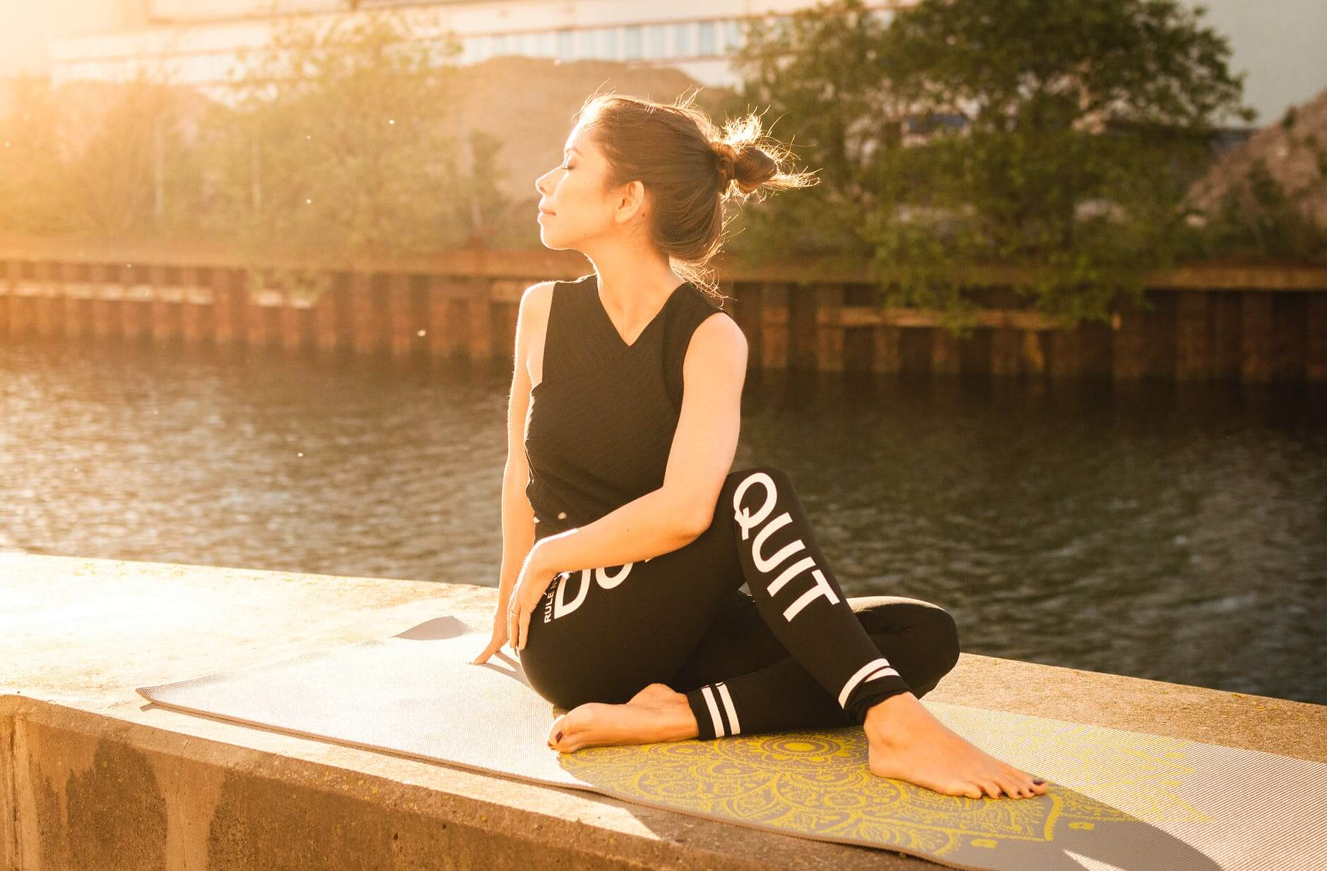 self-improvement-quotes-tips-woman-wearing-black-fitness-outfit-performs-yoga-near-body-of-water