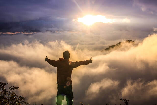 man-mountaintop-clouds